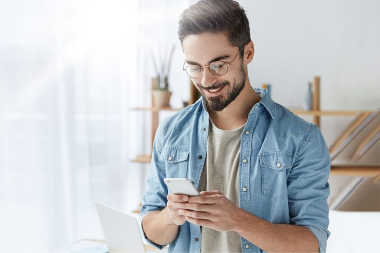Man wearing glasses while looking at his phone