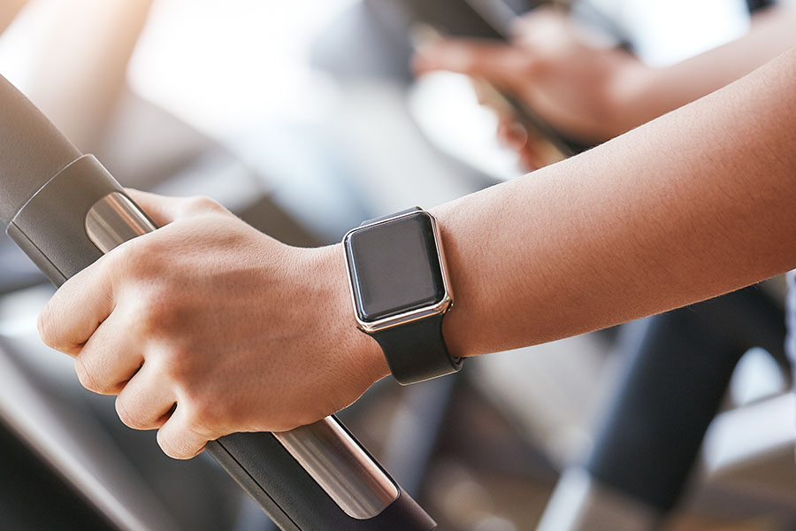 Close-up photo of smart watch on woman hand holding the handle of cardio machine in gym