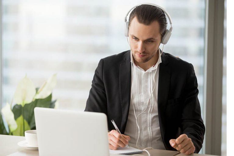 Businessman in headphones taking notes in front of laptop.