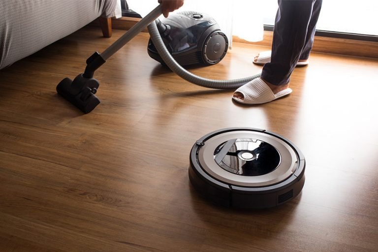 Robot vacuum cleaner with a person using a normal vacuum behind it