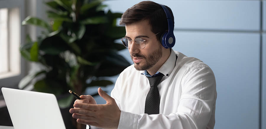 Businessman in headphones makes videocall chatting with partner consulting client