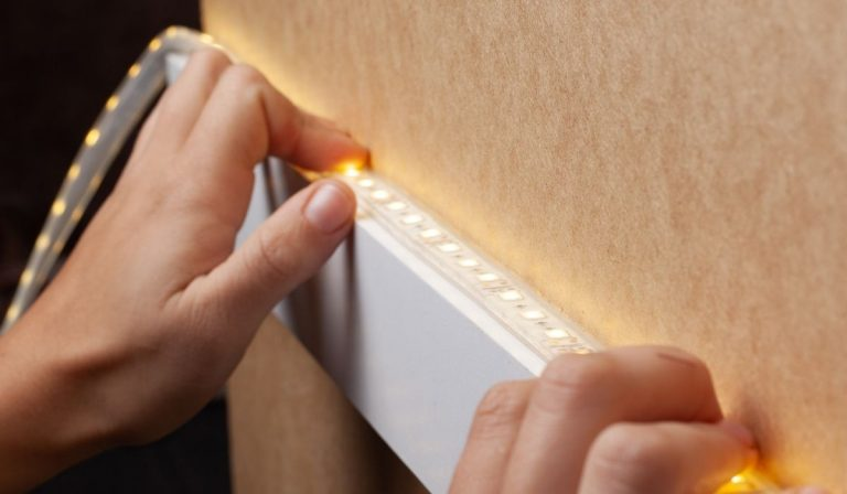 Person sticking LED strip to a wooden shelf