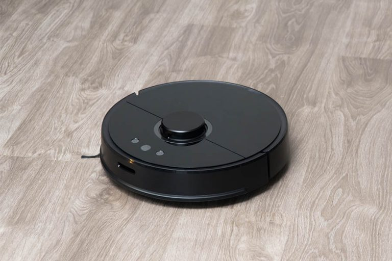 Robot vacuum cleaner black on the floor is cleaning, gray laminate