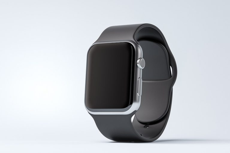 Smart watch with black strap on a white table