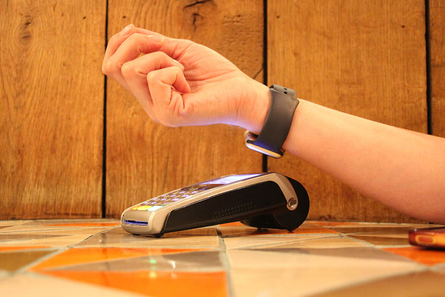 Contactless payment smartwatch pdq with hand holding credit card to pay