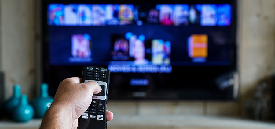 Hand with a remote control with a tv in the background, sliding through apps