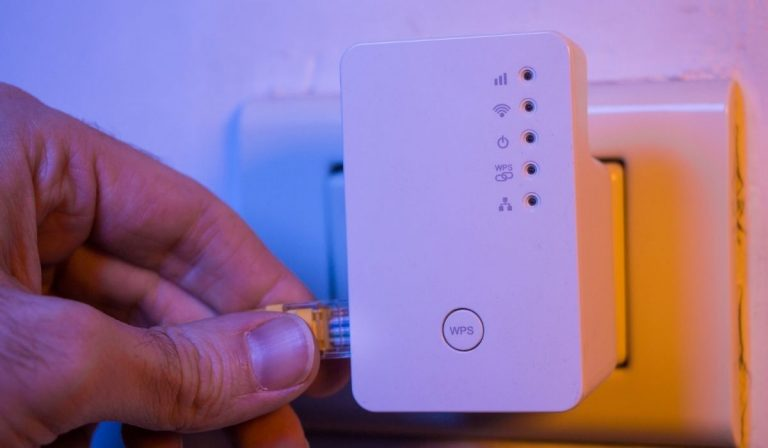 Man insert ethernet cable into WiFi extender device